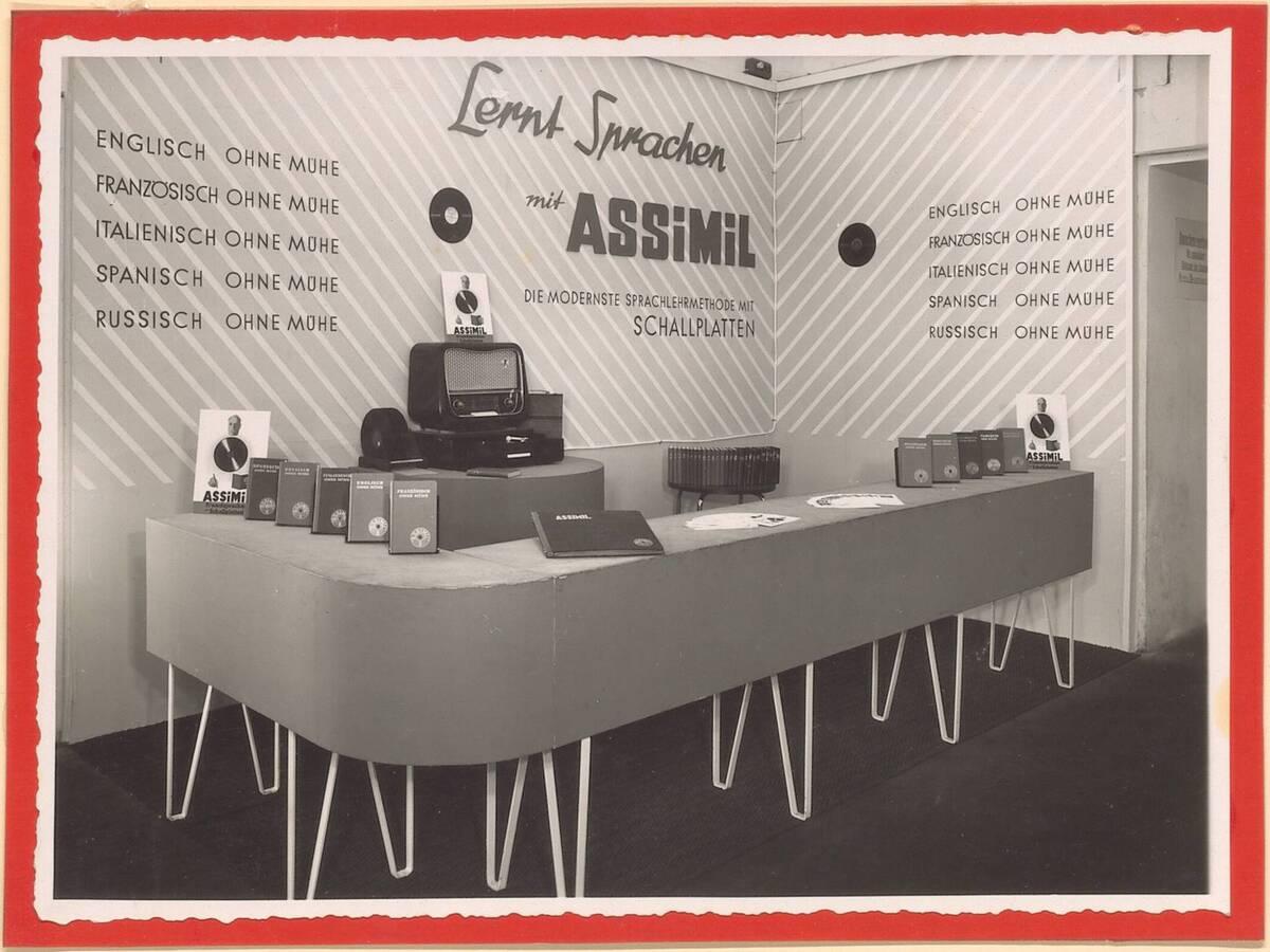 Fotografie einer Auslagengestaltung, bzw. eines Werbestandes mit Radio, Büchern und Schallplatten der Firma Assimil, ausgeführt von der Firma Hrachowina, von 1929-1950 (vom Bearbeiter vergebener Titel) von Anonym
