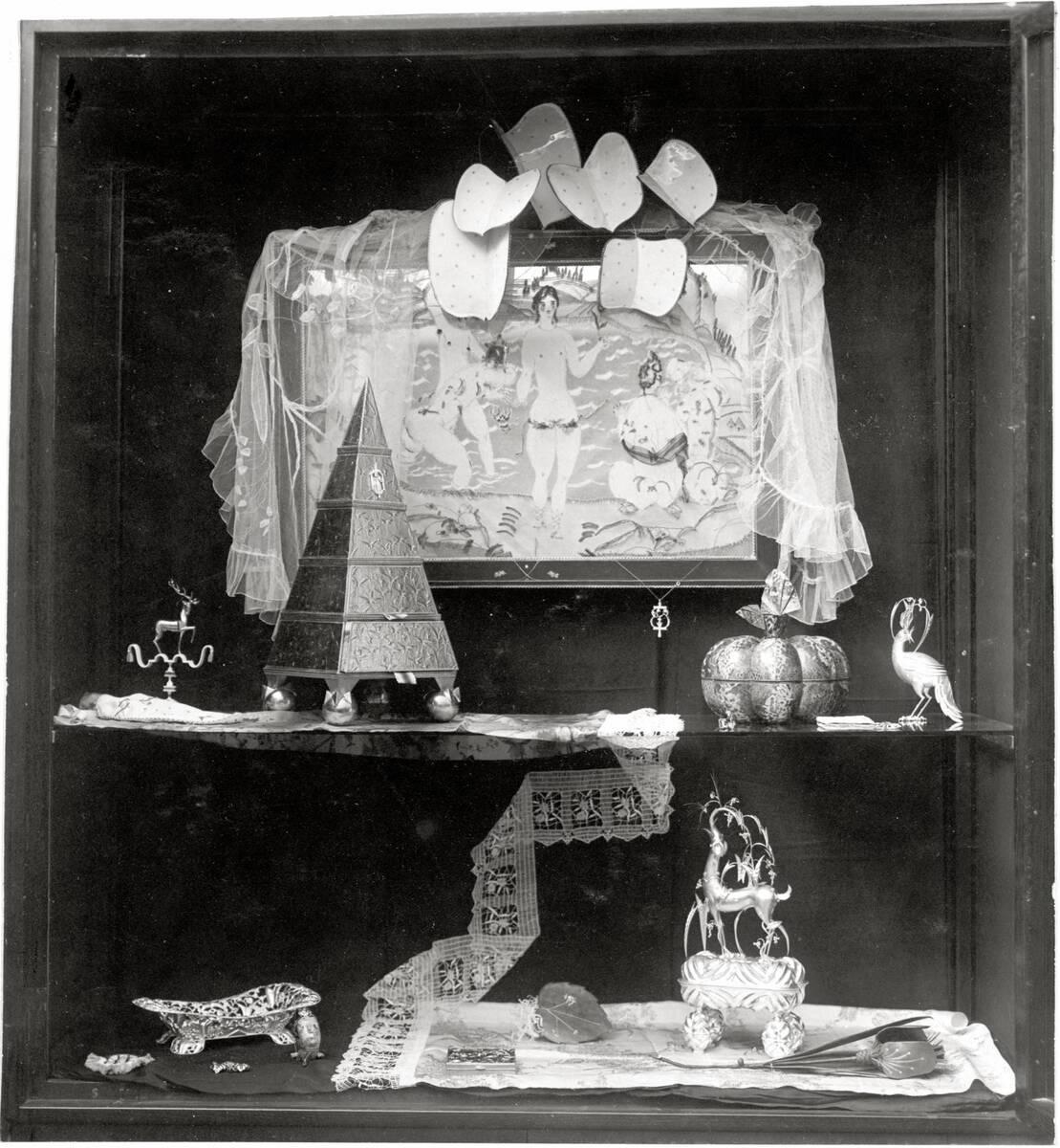 """Vitrine auf der Kunstschau 1920 im Österreichischen Museum für Kunst und Industrie, Wien I, Wollzeile 45 (heute Weiskirchnerstraße 3): """"Aufsatz mit Hirsch"""", """"Schachtelpyramide"""", """"Kürbis"""", """"Vogel"""", """"Brotkorb"""", """"Dose"""" mit Reh von Peche, Dagobert"""